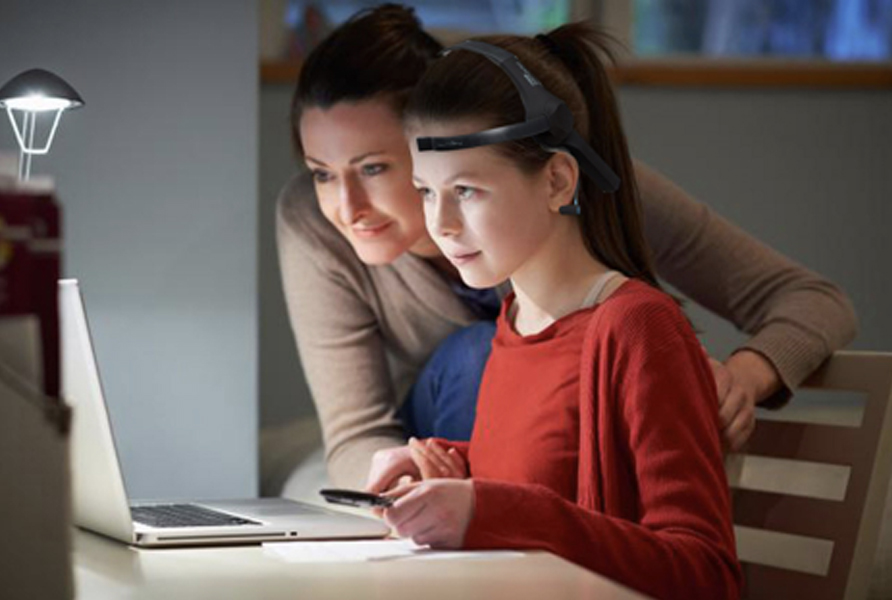 Child studying with parent wearing eeg headset